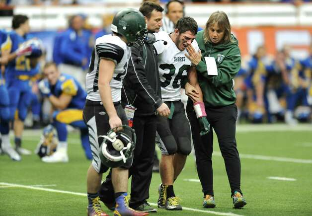 Schalmont's quarterback Nick Gallo, second from right, gets assistance from coach Joe Whipple, center, and others after a game-ending injury for Gallo in their Class B state football final against Maine-Endwell on Sunday Nov. 30, 2014, at the Carrier Dome in Syracuse, N.Y. (Cindy Schultz / Times Union) Photo: Cindy Schultz / 00029662A
