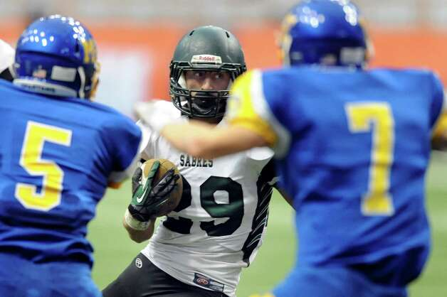 Schalmont's Kyle Strube, center, carries the ball as Maine-Endwell's Adam Gallagher, left, and Kevin Barrett defend during their Class B state football final against Maine-Endwell on Sunday Nov. 30, 2014, at the Carrier Dome in Syracuse, N.Y. (Cindy Schultz / Times Union) Photo: Cindy Schultz / 00029662A
