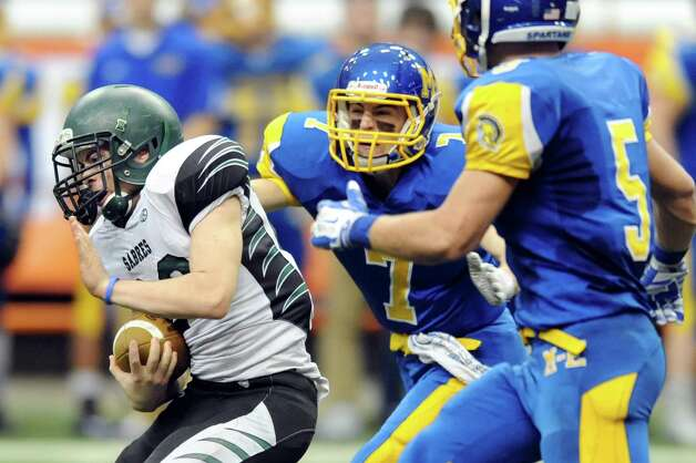 Schalmont's Cameron Brooks, left, gains yards as Maine-Endwell's Kevin Barrett, center, and Adam Gallagher defend during their Class B state football final against Maine-Endwell on Sunday Nov. 30, 2014, at the Carrier Dome in Syracuse, N.Y. (Cindy Schultz / Times Union) Photo: Cindy Schultz / 00029662A