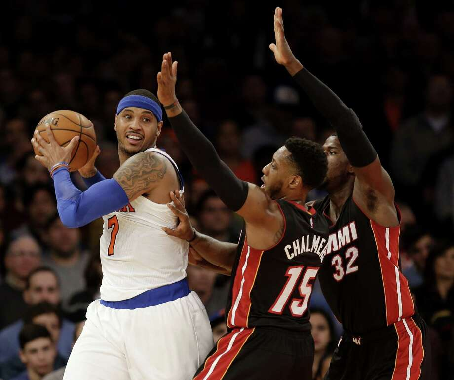 New York Knicks' Carmelo Anthony, left, looks to pass around Miami Heat's James Ennis, right, and Mario Chalmers during the first half of the NBA basketball game, Sunday, Nov. 30, 2014 in New York. (AP Photo/Seth Wenig) ORG XMIT: NYSW118 Photo: Seth Wenig / AP