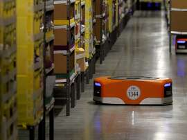 A Kiva robot goes in search of a stack of merchandise at the factory Sunday November 30, 2014. Amazon.com Inc. unveiled its eighth generation fulfillment center in Tracy, Calif. which utilizes robotics, Kiva technology, vision systems and software to quickly fulfill holiday orders across the country.
