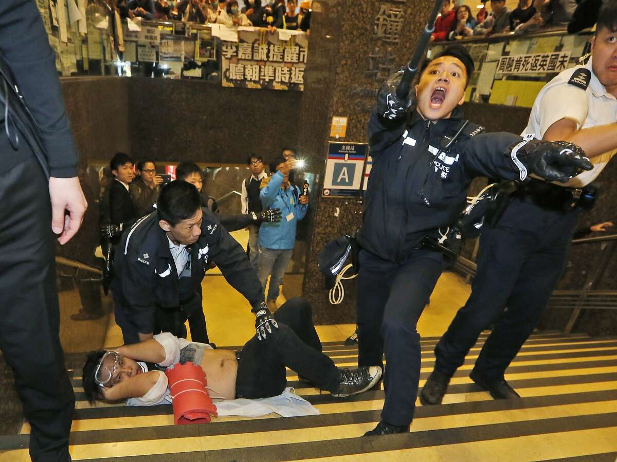 A protester lies on the stairway as police try to remove him and others from a tube station near government headquarters in Hong Kong Monday, Dec. 1, 2014. Pro-democracy protesters clashed with police as they tried to surround Hong Kong government headquarters late Sunday, stepping up their movement for genuine democratic reforms after camping out on the city's streets for more than two months. (AP Photo/Kin Cheung)