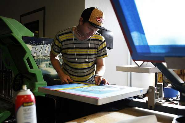 Chris Cook, of Sugabus Media, screen prints t-shirts for a client at TechShop on November 13, 2014 in San Francisco, Calif.