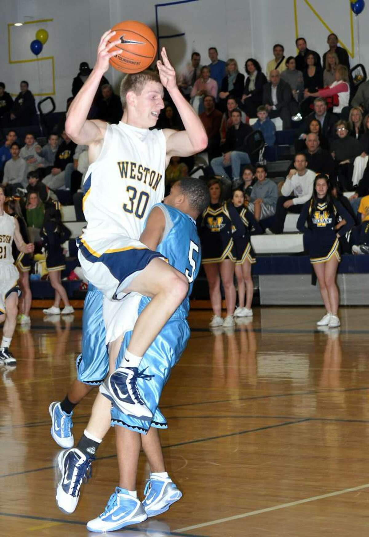 Weston's Dennis Levene collides with a Kolbe Cathedral defender as he attempts a shot during the second period of Monday's boys basketball game at Weston High School.