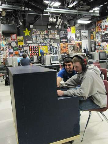 "Staples High School juniors DJ Sixsmith, left, and Eric Gallanty, right, use the ""piano bar,"" a portable radio station built by Faculty Adviser Jim Honeycutt. Photo: Kirk Lang / Westport News"