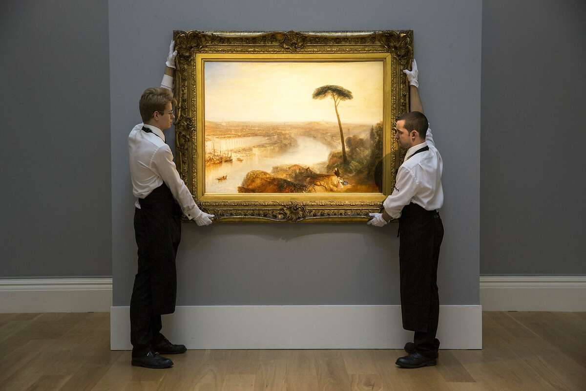 LONDON, ENGLAND - NOVEMBER 28: Gallery technicians at Sotheby's auction house adjust 'Rome, from Mount Aventine' by J.M.W. Turner on November 28, 2014 in London, England. The painting, one of the few major works by Turner still privately owned, is on exhibition in London ahead of its auction in the 'Old Master and British Paintings Evening Sale' at Sotheby's on December 3, 2014 where it is expected to fetch in excess of 15 million GBP. (Photo by Rob Stothard/Getty Images) ***BESTPIX***