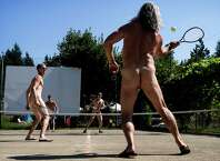 Groups of active participants take to the tennis courts for several rounds of sunny sporting during Fraternity Snoqualmie's annual optional nude concert and celebration, Nudestock, on Saturday, August 23, 2014, in Issaquah, Washington. Nudestock, one of the park's largest crowd-drawing events, boasts free reign to swimming pools, campgrounds and live music - with many of the musicians playing in their birthday suits.