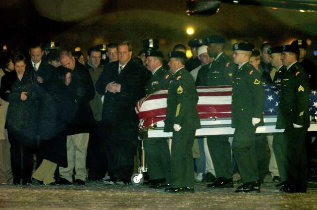 Members of the military carry the casket containing the remains of U.S. Army Sgt.  David Fisher at Albany International Airport in Colonie on Dec. 6, 2004. (Michael P. Farrell/Times Union) Photo: MICHAEL P. Farrell / ALBANY TIMES UNION