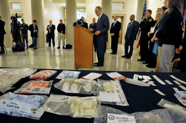 "Seized heroin in evidence bags is seen on a table as Senator Chuck Schumer, background center, addresses those gathered at a press conference at the Albany County Courthouse on Monday, Dec. 1, 2014, in Albany, N.Y.  The press event was held for Senator Chuck Schumer to talk about his proposal for $100 million in federal funding to create a law enforcement ""heroin surge"" to combat the drug.  (Paul Buckowski / Times Union) Photo: Paul Buckowski / 00029667A"