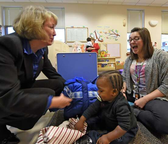 Rensselaer County Executive Kathy Jimino, left, assists Joshua Yarrell, center, with his new winter coat as teacher's assistant Dayna Sokol watches Monday morning, Dec. 1, 2014, at the CEO Family Resource Center in Troy, N.Y., during a Coats for Kids program event. (Skip Dickstein/Times Union) Photo: SKIP DICKSTEIN / 00029636A