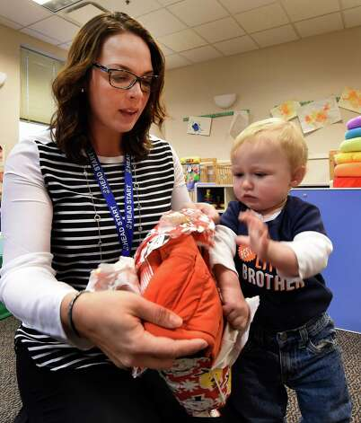 Teacher Heidi Pascarella, helps Max Matala unwrap his new winter coat Monday morning, Dec. 1, 2014, at the CEO Family Resource Center in Troy, N.Y., during a Coats for Kids program event. (Skip Dickstein/Times Union) Photo: SKIP DICKSTEIN / 00029636A