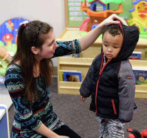 Home visit teacher Kristin Breen helps fit Israel Allen with a new winter coat Monday morning, Dec. 1, 2014, at the CEO Family Resource Center in Troy, N.Y., during a Coats for Kids program event. (Skip Dickstein/Times Union) Photo: SKIP DICKSTEIN / 00029636A