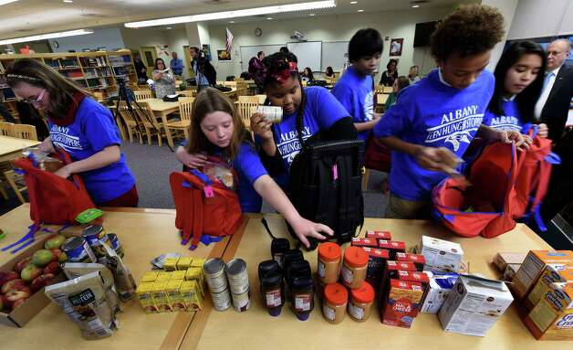 Students from the Myers Middle School load up backpacks with food Monday morning Dec. 1, 2014 in Albany, N.Y.  The students are involved in the Children Helping Children in the Fight Against Hunger program at the school. (Skip Dickstein/Times Union) Photo: SKIP DICKSTEIN / 00029657A