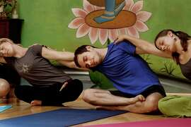 Jeremy Simon (center) leads the group in some yoga exercises. One of the newest sensations is acro yoga with live singing crystal bowls, as practiced at a training at Yogatree in San Francisco, CA Sunday July 19, 2009.