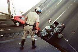 FILE - In this Oct. 17, 1989 file photo, a California Highway Patrol officer checks the damage to cars that fell when the upper deck of the Bay Bridge collapsed onto the lower deck after the Loma Prieta earthquake in San Francisco. Crowded roadways and packed buses, trains and ferries are on tap for commuters starting Wednesday night, Aug. 28, 2013 when officials shut down the San Francisco-Oakland Bay Bridge to traffic in preparation for a new $6.4 billion span opening late Monday, Sept. 2 or early Tuesday.   (AP Photo/George Nikitin, File)