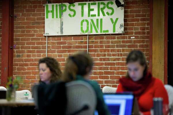 """A """"Hipsters Only"""" sign is displayed as members work at the Impact Hub in Oakland, California, U.S., on Tuesday, Nov. 18, 2014. Oakland, long synonymous with crime and blight, is attracting businesses and residents priced out of its more famous neighbor, San Francisco and drawn to an increasingly vibrant scene. Photographer: David Paul Morris/Bloomberg"""