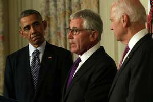 U.S. Secretary of Defense Chuck Hagel (C) speaks as President Barack Obama (L) and Vice President Joe Biden look on during a press conference announcing Hagel's resignation.