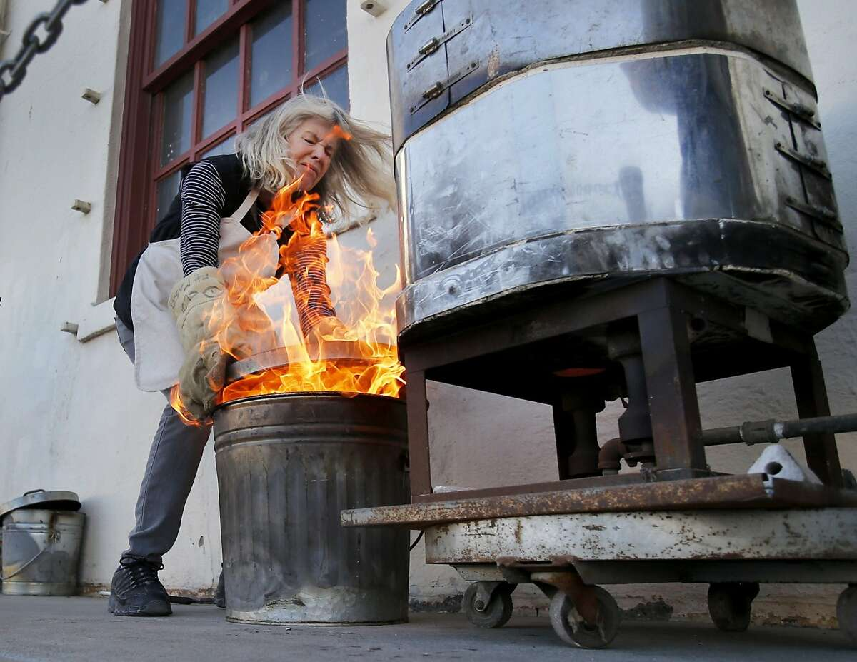Glenda Hamilton helps a ceramic student with his Raku ware in the rear of a Fort Mason building, part of a City College class on ceramics Tuesday November 25, 2014.