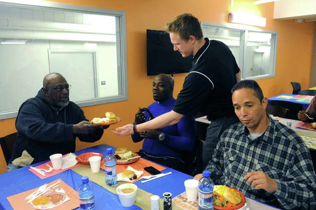 Union College hockey right winger Nick Cruise, center, serves meals during the YMCA men's residence Thanksgiving dinner on Tuesday Nov. 25, 2014 in Schenectady, N.Y. (Michael P. Farrell/Times Union) Photo: Michael P. Farrell, Albany Times Union / 00029632A