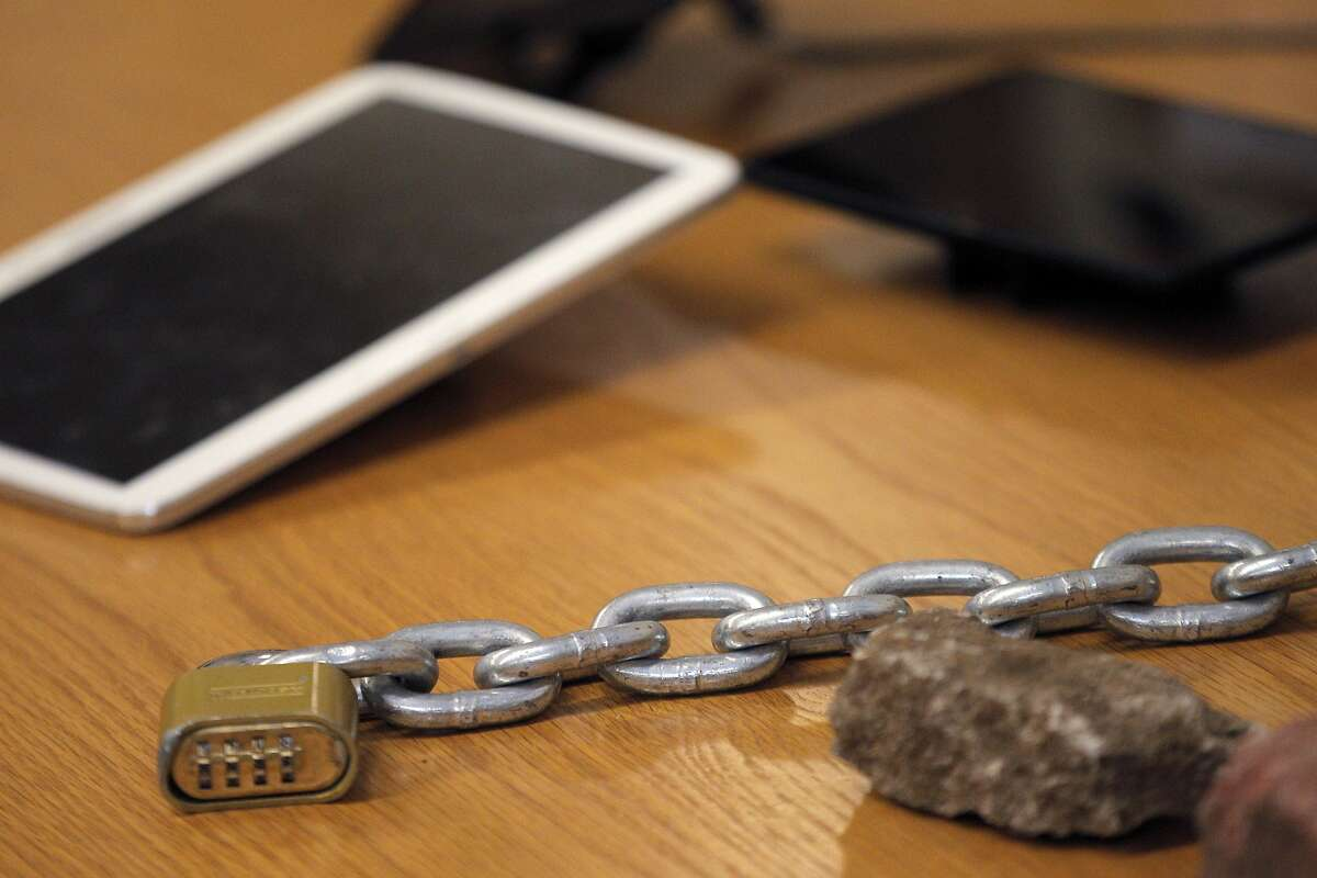 Items including a chain and padlock and stolen electronics that were logged in as evidence by SFPD after arrests for vandalism and assaults against police during Black Friday protests during a press conference at SFPD headquarters in San Francisco, Calif., on Monday, December 1, 2014.