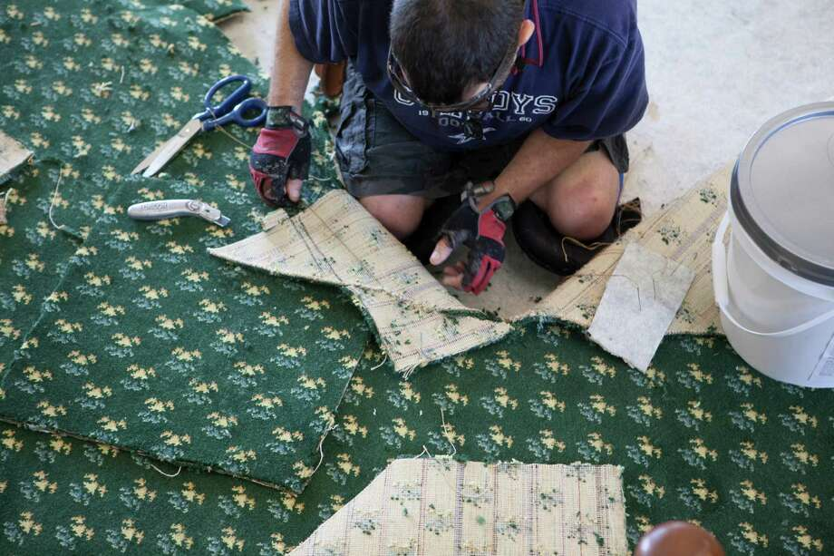 A worker pieces together sections of the original-pattern carpeting on the Senate chamber floor. Photo: Senate Media Services / Texas Senate Media Services