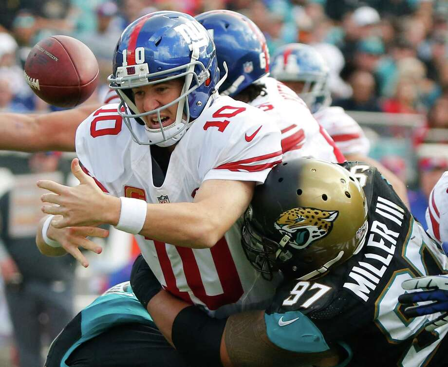 New York Giants quarterback Eli Manning (10) fumbles the ball as he is hit by Jacksonville Jaguars defensive tackle Roy Miller (97) during the second half of an NFL football game in Jacksonville, Fla., Sunday, Nov. 30, 2014. The ball bounced in the end zone and was recovered by Jacksonville for a touchdown. (AP Photo/Stephen B. Morton) ORG XMIT: JVS113 Photo: Stephen B. Morton / FR56856 AP