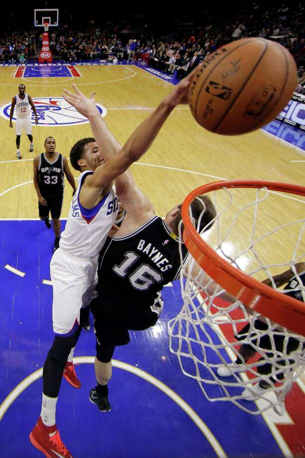 Philadelphia 76ers' Michael Carter-Williams, left, tries to dunk the ball against San Antonio Spurs' Aron Baynes, of Australia, during the first half of an NBA basketball game, Monday, Dec. 1, 2014, in Philadelphia. (AP Photo/Matt Slocum) ORG XMIT: PXC108 Photo: Matt Slocum / AP