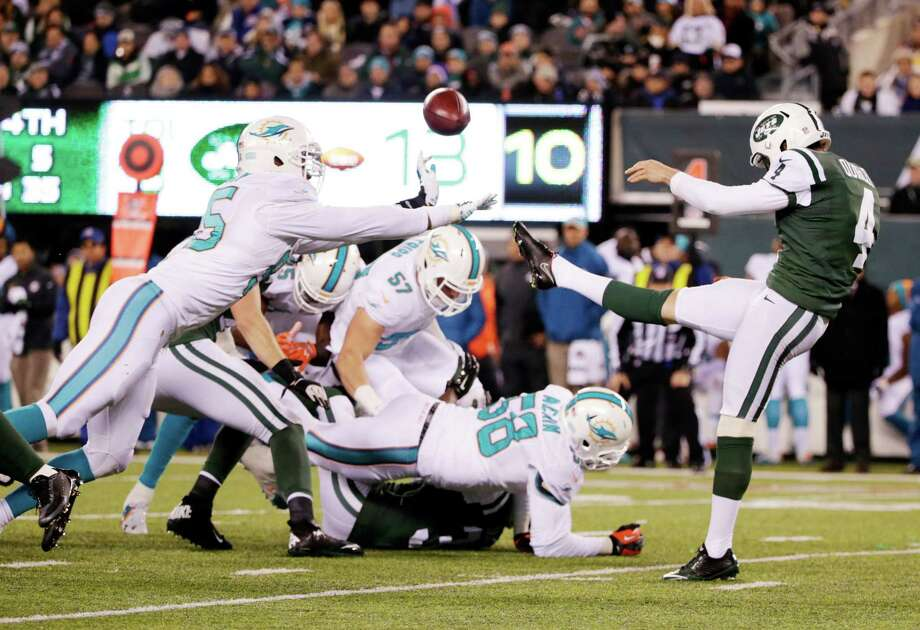 Miami Dolphins defensive end Dion Jordan (95) blocks a punt by New York Jets punter Ryan Quigley (4) during the third quarter of an NFL football game, Monday, Dec. 1, 2014, in East Rutherford, N.J. (AP Photo/Julio Cortez)  ORG XMIT: ERU Photo: Julio Cortez / AP