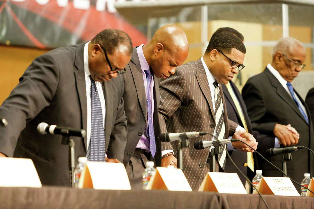 Panelists pray before speaking at a town hall in which discussion took place about how the crisis in Ferguson reminds us that we have more work to do in Houston, Monday, Dec. 1, 2014 in Houston.
