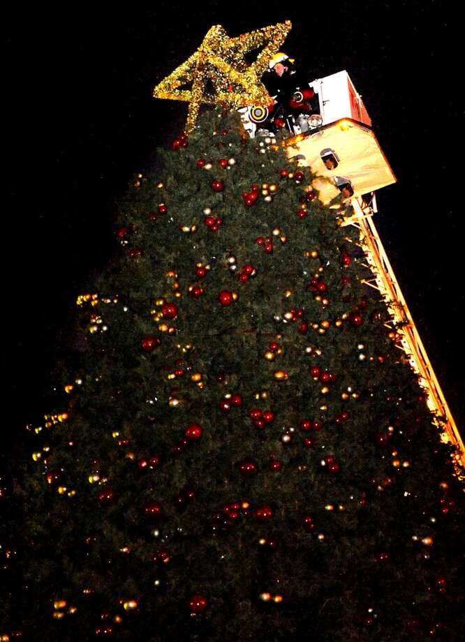The Beaumont Fire Department places the star on top of the city Christmas Tree downtown in Beaumont, Thursday. Tammy McKinley/ The Enterprise Photo: Tammy McKinley/ The Enterprise