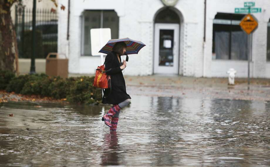 """Headed to work, Linda Davis, of Oakland, walks through a flooded intersection on Lakeshore Avenue on Tuesday Dec. 2, 2014 in Oakland, Calif. """"It's really deep,"""" said Davis. Photo: Mike Kepka, The Chronicle"""