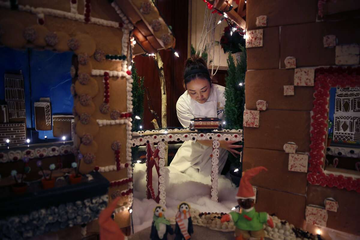Renee Cade, executive pastry chef, moves a Christmas Tree into position while decorating the Grand Gingerbread Display at the Palace Hotel on Monday, December 1, 2014 in San Francisco, Calif.