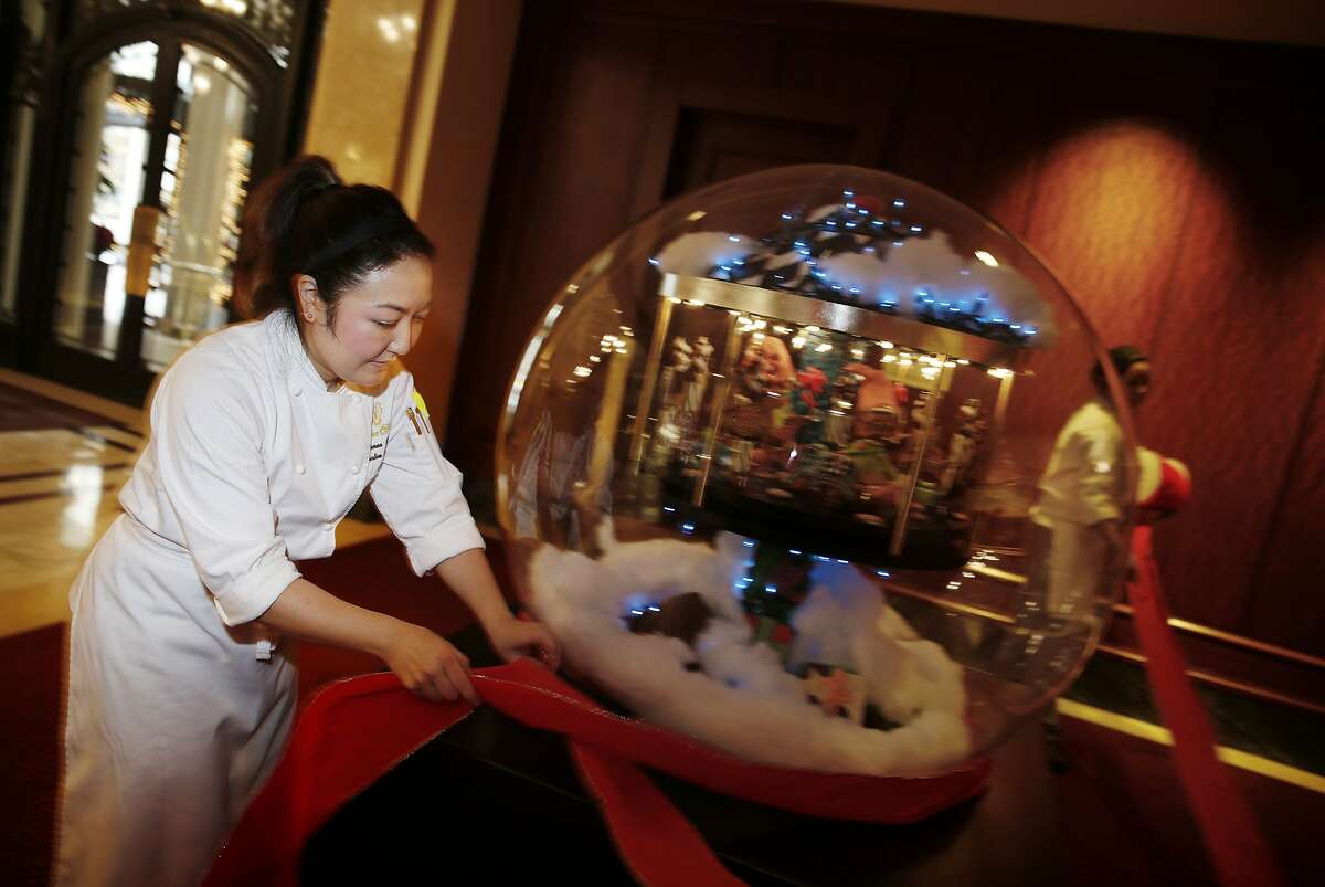 Renee Cade (l to r), executive pastry chef, and Tia O'Neel, pastry cook, work together while decorating a giant snow globe with a ribbon at the Palace Hotel on Monday, December 1, 2014 in San Francisco, Calif.