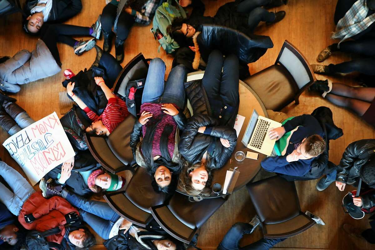 """PLEASE DON'T DIE ON MY TERM PAPER: In St. Louis, Washington University sophomore Nick Williams (right) tries to get some work done as fellow students stage a """"die-in"""" on his table and around him to draw attention to perceived police abuse in the Ferguson case."""