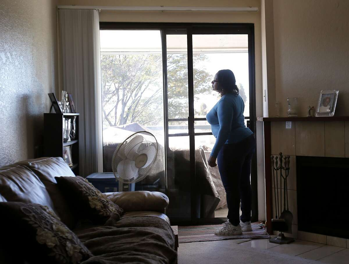 Nichelle Lacy looks out her balcony window in her apartment Monday November 24, 2014. Nichelle Lacy is thankful for Season of Sharing for helping her with the apartment rent after losing her job recently. She lives in Hayward, Calif. with her daughter Amani.