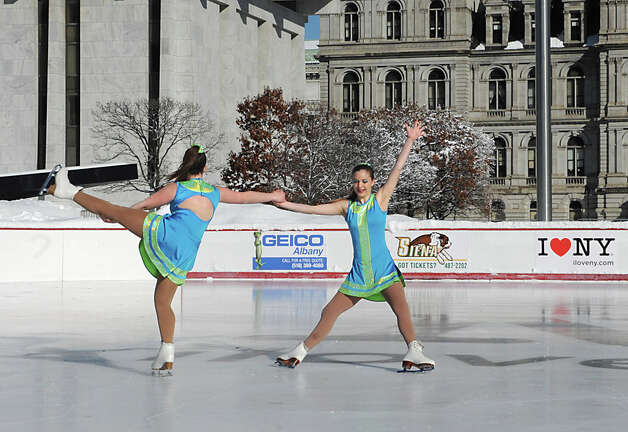 Skaters Allie Murray, 15, left, and Samantha Rydzewski, 15, from Saratoga Synchronized Skating perform on the opening day of the ice rink located on the Empire State Plaza on Friday, Nov. 28, 2014 in Albany, N.Y. The rink will be open 7 days a week from 11:00 am - 8:00 pm and skating is free. Hannaford sponsors free skate rental on Fridays. (Lori Van Buren / Times Union) Photo: Lori Van Buren, Albany Times Union / 00029292A
