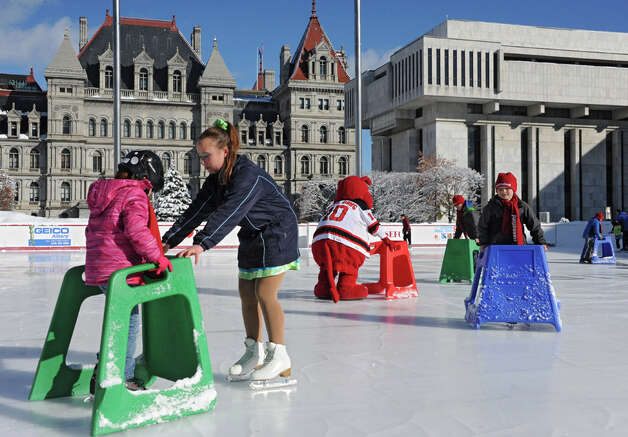 Ashley Glockler, 7, of Clifton Park, left, gets her first skating lesson from Allie Murray, 15, of Saratoga Sychronized Skating during opening day of the ice rink located on the Empire State Plaza on Friday, Nov. 28, 2014 in Albany, N.Y. The rink will be open 7 days a week from 11:00 am - 8:00 pm and skating is free. Hannaford sponsors free skate rental on Fridays. (Lori Van Buren / Times Union) Photo: Lori Van Buren, Albany Times Union / 00029292A