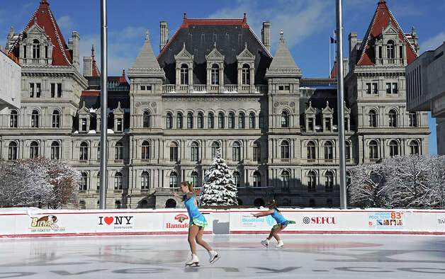 Skaters Samantha Rydzewski, 15, left, and Allie Murray, 15, from Saratoga Synchronized Skating perform on the opening day of the ice rink located on the Empire State Plaza on Friday, Nov. 28, 2014 in Albany, N.Y. The rink will be open 7 days a week from 11:00 am - 8:00 pm and skating is free. Hannaford sponsors free skate rental on Fridays. (Lori Van Buren / Times Union) Photo: Lori Van Buren, Albany Times Union / 00029292A