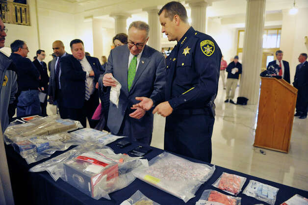 "Senator Chuck Schumer, left, and Albany County Sheriff Craig Apple look at bags of seized heroin at a press conference at the Albany County Courthouse on Monday, Dec. 1, 2014, in Albany, N.Y.  The press event was held for Senator Chuck Schumer to talk about his proposal for $100 million in federal funding to create a law enforcement ""heroin surge"" to combat the drug.  (Paul Buckowski / Times Union) Photo: Paul Buckowski, Albany Times Union / 00029667A"