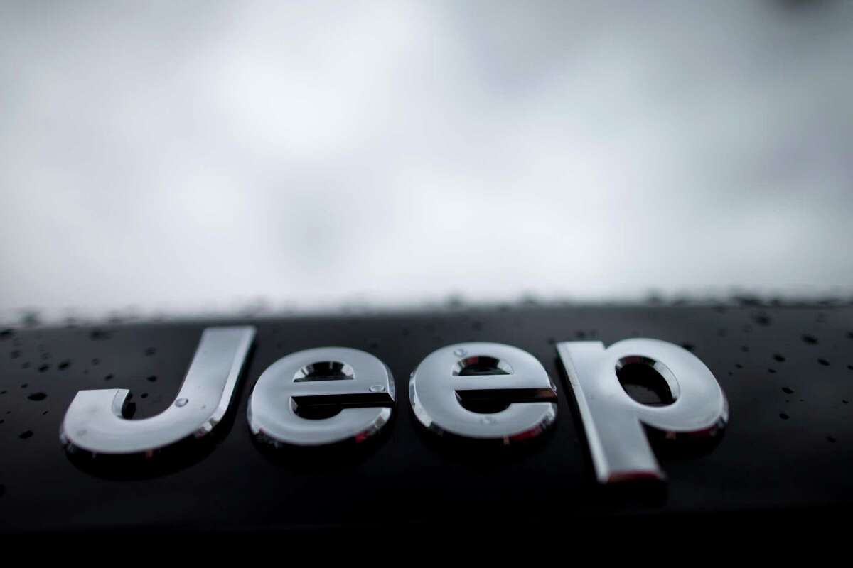 Rain drops dot the Jeep emblem on a Grand Cherokee SUV at a dealership lot Tuesday, Dec. 2, 2014, in San Diego. Black Friday promotions - coupled with falling gas prices, low-interest loans and hot new vehicles - drove U.S. auto sales higher in November, kicking off what's expected to be a strong holiday season. Chrysler, which sells Jeep cars, posted its best November in 13 years. (AP Photo/Gregory Bull)