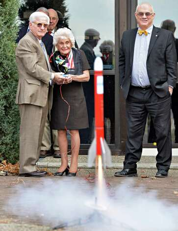 Neil and Jane Golub, left, launch a model rocket as miSci executive director Dr. Mac Sudduth, right, watches during ceremonies to launch miSci's new Challenger Learning Center Tuesday, Dec. 2, 2014, at miSci in Schenectady, N.Y. The Challenger Learning Center is based on the space shuttle and NASA space exploration program. It will include classroom study activities to help students apply and enhance their decision-making skills, solve problems and communicate. (John Carl D'Annibale / Times Union) Photo: John Carl D'Annibale / 00029688A