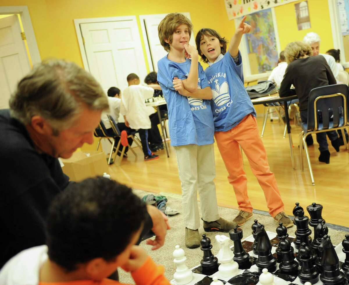 Brunswick School fifth graders Lucas Korn, left, and Max Konzerowsky watch students play chess at the InspiraKing Chess Club at the Inspirica children's shelter in Stamford, Conn. Monday, Dec. 1, 2014. Korn and Konzerowsky started the club to share their love of chess with children at the shelter while helping them build strategic and creative thinking skills.