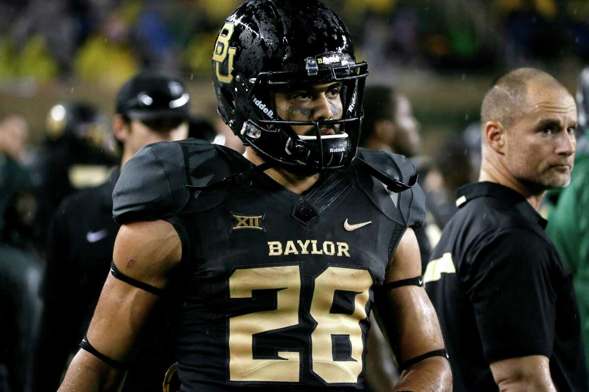 Baylor running back Devin Chafin (28) walks through the team bench area watching play against Oklahoma State during an NCAA college football game, Saturday, Nov. 22, 2014, in Waco, Texas. (AP Photo/Tony Gutierrez)