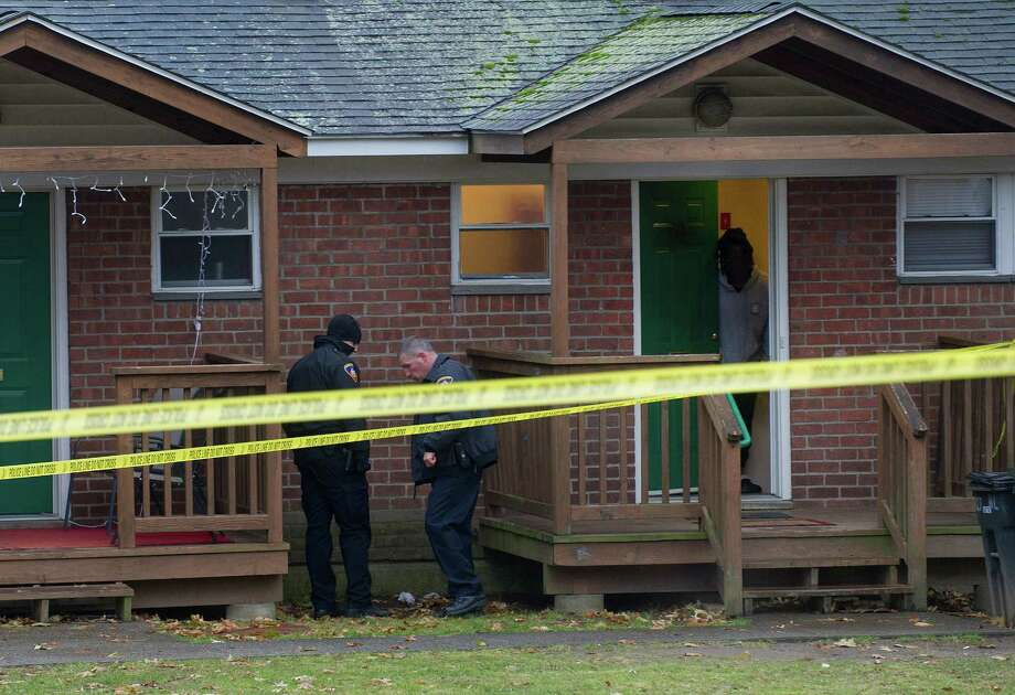 Police officers look over the crime scene on Myano Lane on Tuesday, December 2, 2014, where shots were fired late Monday night and again Tuesday afternoon, when a victim was grazed with a bullet. Photo: Lindsay Perry / Stamford Advocate