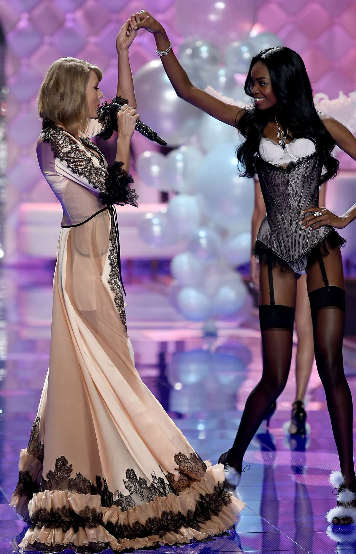 Model Maria Borges (R) and singer Taylor Swift are seen on the runway during the 2014 Victoria's Secret Fashion Show at Earl's Court Exhibition Centre on December 2, 2014 in London, England.