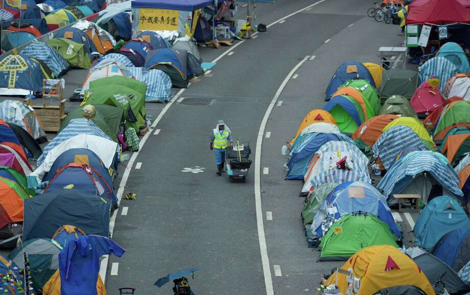 "A street cleaner pushes her cart between rows of tents at the pro-democracy movement's main protest site in the Admiralty district of Hong Kong early on December 3, 2014. The original founders of Hong Kong's pro-democracy Occupy movement tearfully announced on December 2 they would ""surrender"" by turning themselves in to police and urged protesters on the streets to retreat. AFP PHOTO / JOHANNES EISELEJOHANNES EISELE/AFP/Getty Images Photo: JOHANNES EISELE, Staff / AFP"