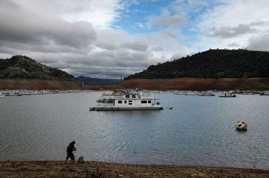 "Joe Cha, 33, fishes at the new water line at Lake Oroville Nov. 29, 2014 in Oroville, Calif. Despite recent rainfall, California's second largest reservoir is near the 1977 historic low at 26 percent of capacity. ""This has been quite the progression,"" said longtime resident Sharon Smith, who has been walking the dam since she moved to the area in 1997. ""It seems like it's happening so fast,"" she said. Photo: Leah Millis / The Chronicle / ONLINE_YES"
