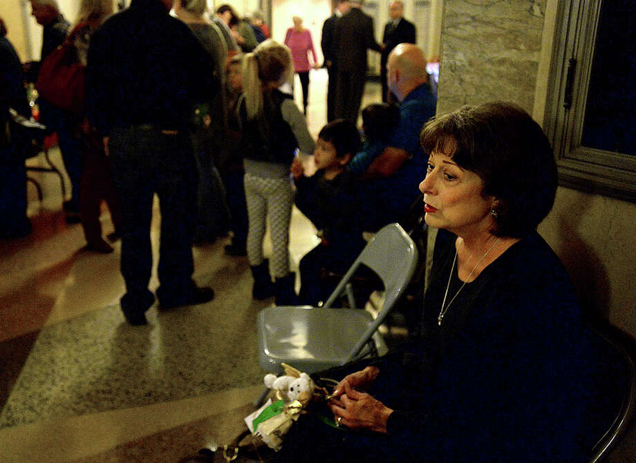 Sherrie Roberts, formerly of Port Arthur and now living in Vinton, LA, somberly sits as the crowds gather for the 14th annual decoration and lighting of the Tree of Angels at the Jefferson County Courthouse Tuesday. Organized by the Coalition for Victims of Violent Crime, ornaments bearing the names of those lost to violent crime are hung, offering friends and loved ones the chance to experience healing and support at the holiday gathering.  Photo taken Tuesday, December 2, 2014 Kim Brent/The Enterprise Photo: KIM BRENT / Beaumont Enterprise