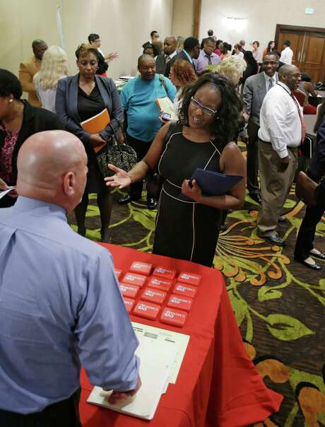 In this Thursday, June 12, 2014 photo, Marsha Lawson talks with a representative from CVS at the Cleveland Career Fair in Independence, Ohio. Optimism among chief executives of large U.S. companies has reached a two-year high, driven by greater optimism about hiring and sales. (AP Photo/Tony Dejak) Photo: Tony Dejak, STF / AP