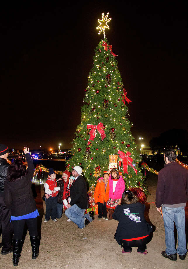Families gather around Universal City's Christmas tree for photos. The tree will remain lit and decorated through the holiday, allowing families to snap holiday portraits right up to Christmas. Photo: Alma E. Hernandez / Alma E. Hernandez / Alma E. Hernandez / For The San
